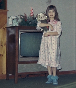 Young child standing next to 1965 Television