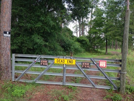 property gate with warning signs