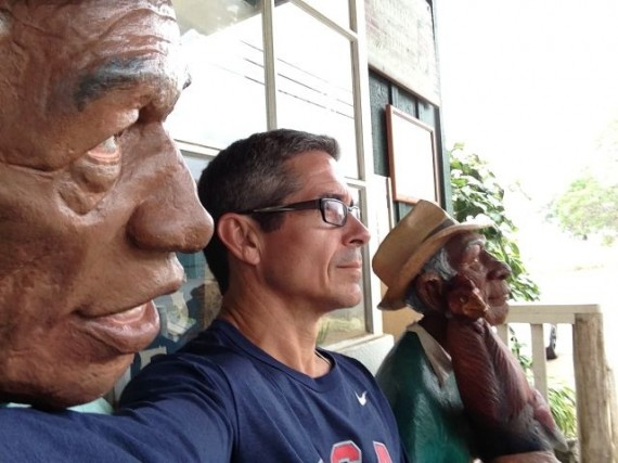 jeff noel sitting between two life-sized human wood carvings