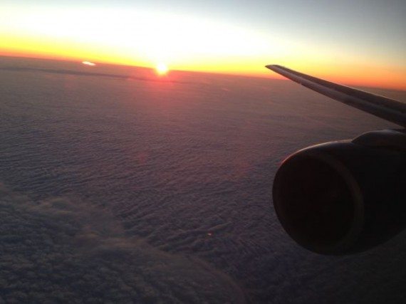 Jet plane cruising above clouds at sunset