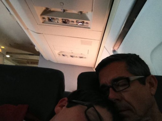 Father and Son nestled close and sleeping on airplane