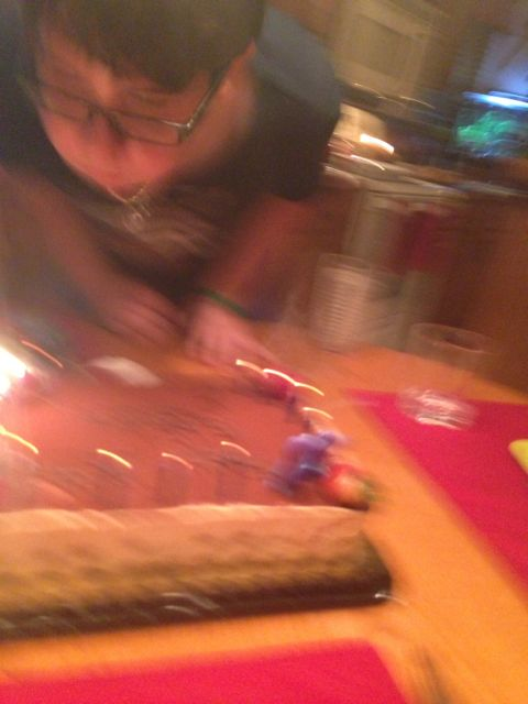 Blurry photo of 13 year old blowing out birthday candles