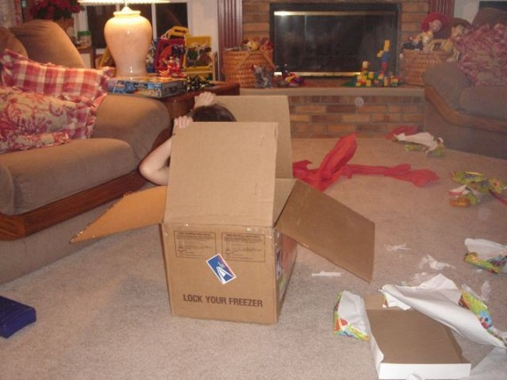 Child playing with box instead of toy inside