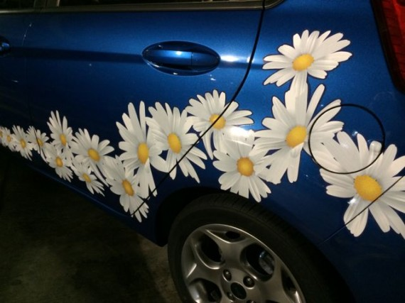 small blue car with daisies painted on side