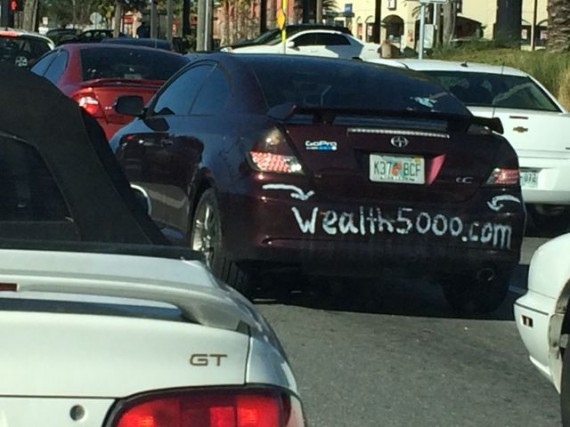 car with wealth building website address painted on bumper