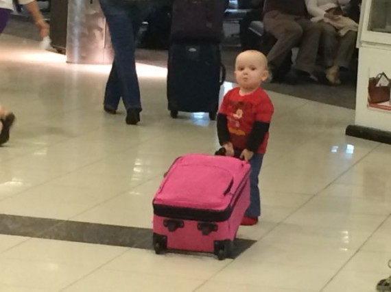 Toddler pulling pink suitcase at airport