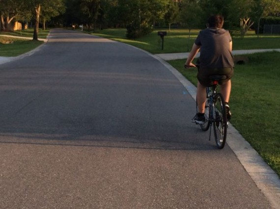 youth riding bike in central Florida neighborhood