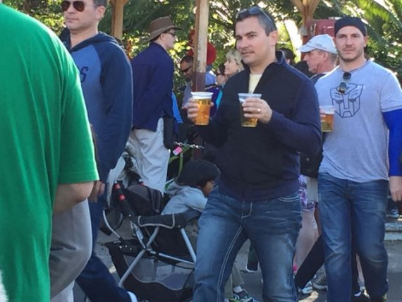 Man carrying a large beer in each hand at Disney