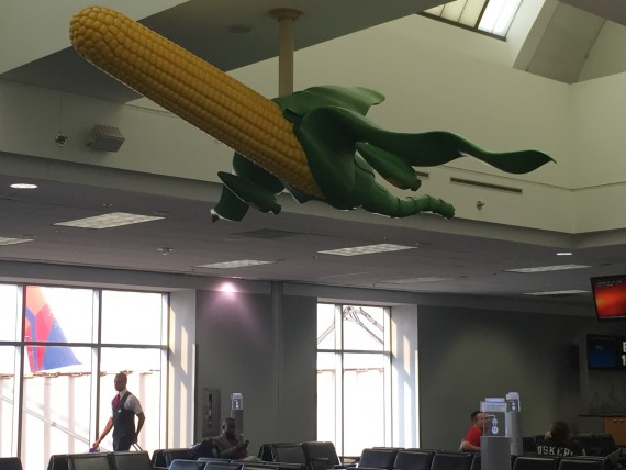 Corn and airplane sculpture hanging from boarding area ceiling