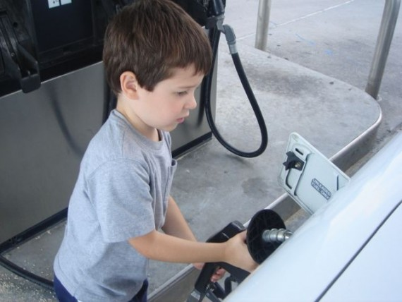 child learning how to put gas in a car